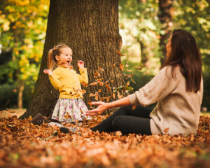Girl playing in the autumn leaves on a photoshoot in Teddington