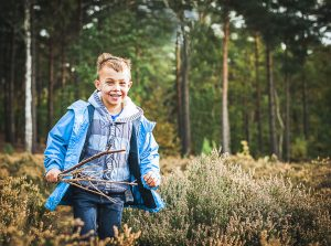 Esher Family Photographer - Young man running through the heather on Esher Commons